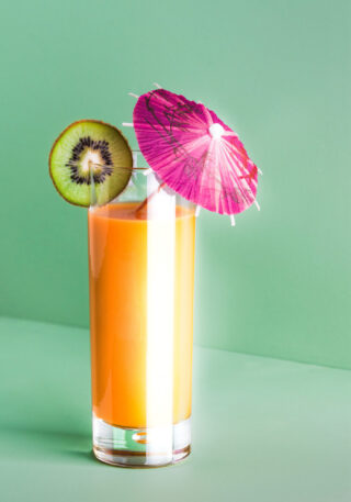 Yellow smoothie in a glass with kiwi and small umbrella