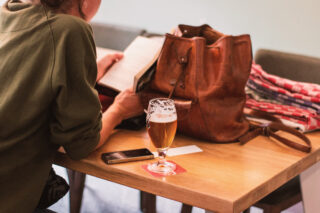 A woman reading a book at a table with a beer glass