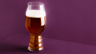 Beer glass in front of purple background